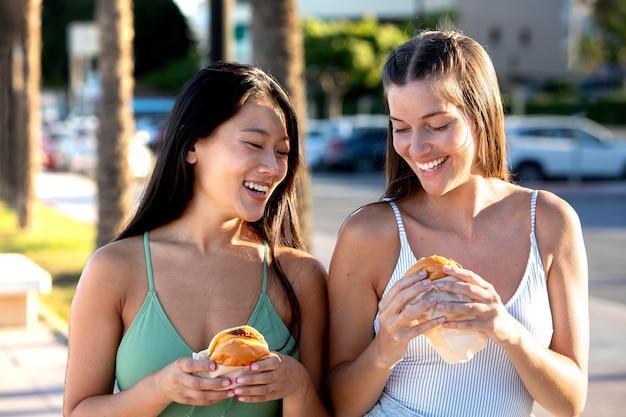 Melhores amigos comendo comida de rua juntos