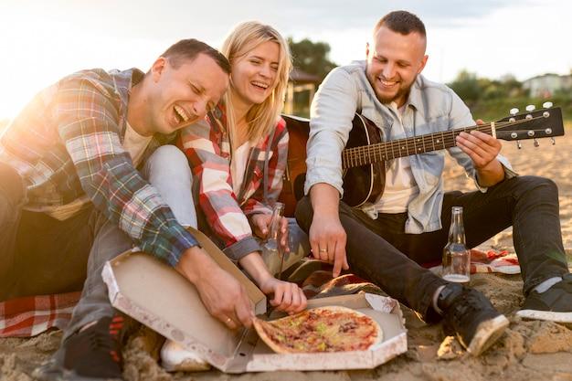 Melhores amigos comendo pizza na praia