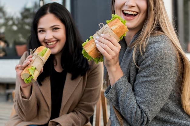 Melhores amigos comendo um sanduíche juntos