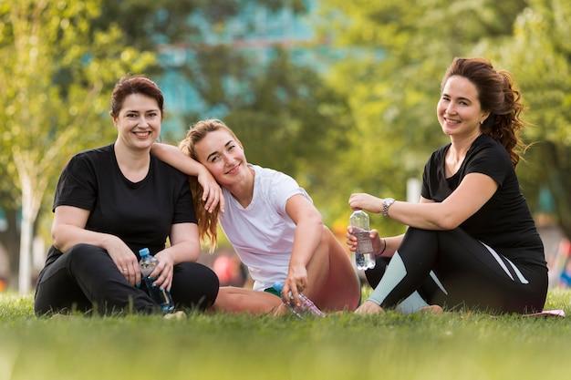 Melhores amigos de frente sentados na grama, vestindo roupas esportivas
