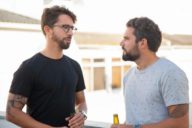 Melhores amigos do sexo masculino discutindo questões sobre garrafa de cerveja