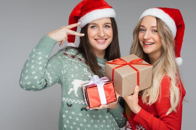 Melhores amigos em chapéus de papai noel com presentes de natal.