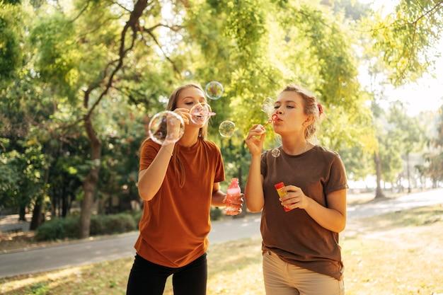 Melhores amigos fazendo bolhas de sabão juntos