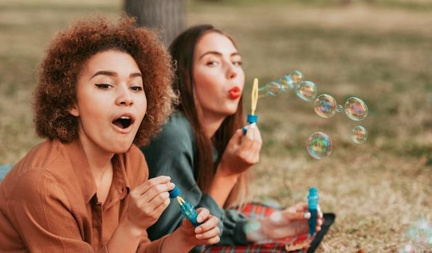 Melhores amigos fazendo bolhas de sabão no outono