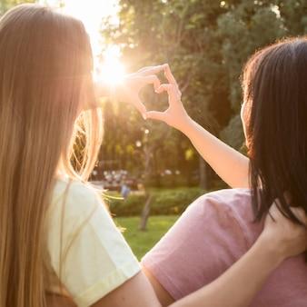 Melhores amigos fazendo um coração na luz do sol
