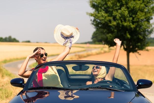 Melhores amigos fazendo um passeio de verão em um carro conversível passando por um campo