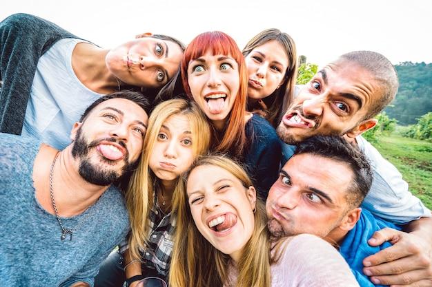 Melhores amigos tirando selfie engraçado em excursão de piquenique mostrando a língua - conceito de estilo de vida jovem com jovens se divertindo juntos ao ar livre - filtro brilhante e quente com foco nas faces centrais