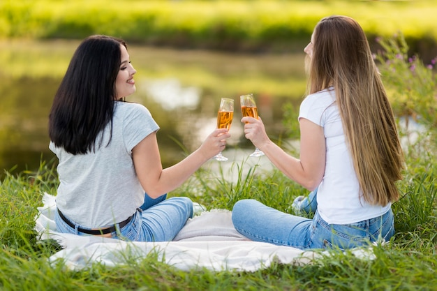 Melhores amigos torcendo com algumas taças de vinho do lado de fora