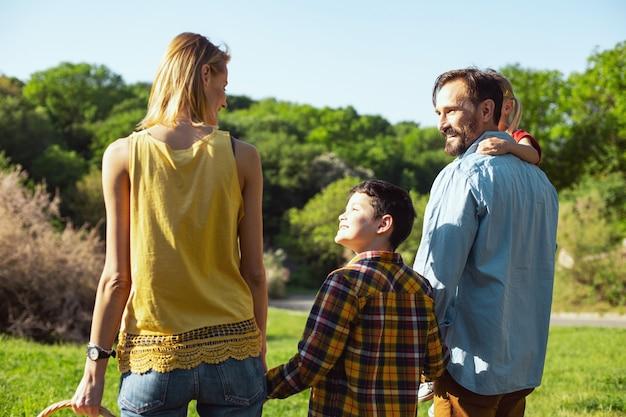 Melhores pais. menino alegre de cabelos escuros caminhando com os pais e a irmã e sorrindo