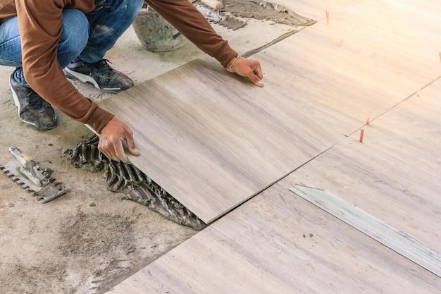 Melhoria de casa, renovação - ladrilhador de trabalhador de construção está ladrilhando