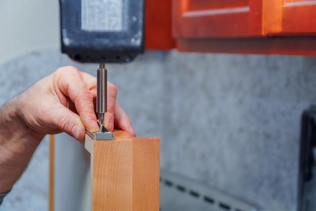 Melhoria home e conceitos de design de interiores. contratante que instala a dobradiça nova da prateleira do armário de cozinha