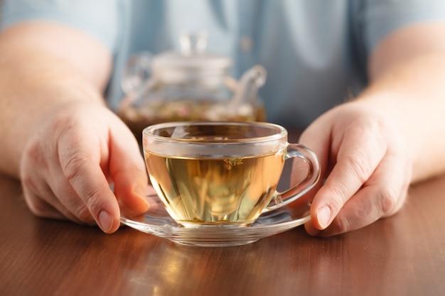 Melicio mãos e copo de vidro de medicamento chá de ervas