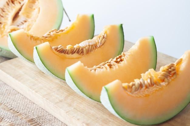 Melões frescos cortados na placa de estaca de madeira. fruta saudável foco seletivo