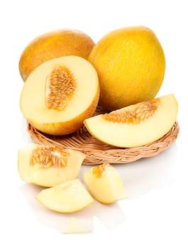 Melões maduros em berço de vime em branco