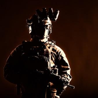 Membro das forças de elite do exército, infantaria moderna com rosto escondido, munição tática, fone de ouvido de rádio equipado, dispositivo de visão noturna montado no capacete, de pé com rifle de serviço de cano curto nas mãos