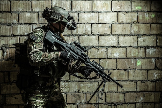 Membro do ranger do exército dos eua com metralhadora e óculos de visão noturna movendo-se ao longo da parede durante a missão