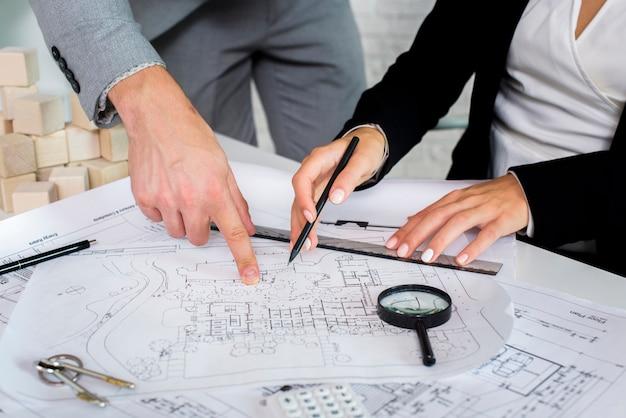 Membros da equipe analisando um plano arquitetônico