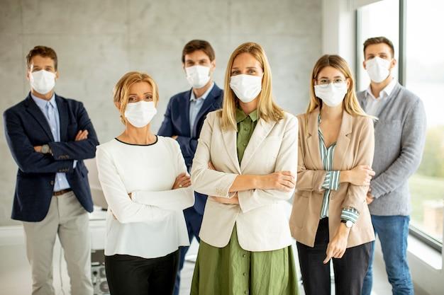 Membros da equipe de negócios com máscaras faciais protetoras e olhando para a câmera no escritório