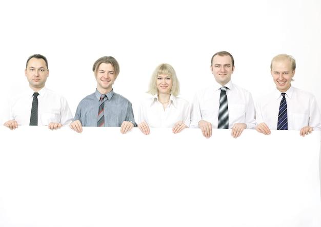 Membros da equipe de negócios segurando uma grande faixa em branco.