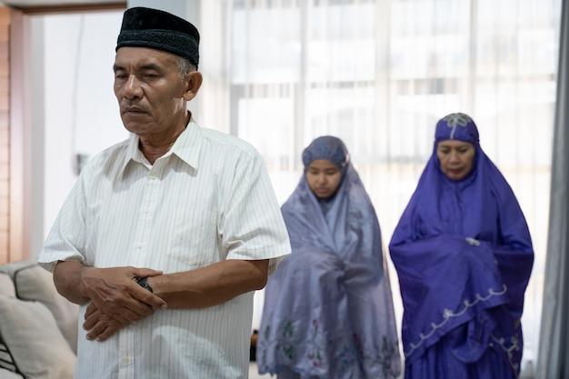 Membros da família orando em congregação na sala de oração