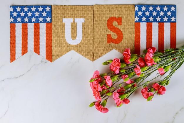 Memorial day, celebração de veteranos com texto de bandeira americana nos em flores de cravo rosa
