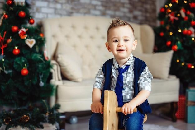 Memórias alegres das férias de natal das crianças. doce menino elegante em uma gravata, cavalgando o cavalo de balanço de madeira. criança feliz e elegante.