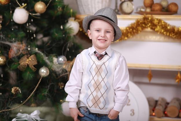 Memórias de infância. menino com chapéu comemorar o natal em casa. menino brincar perto da árvore de natal. feliz e brilhante natal. atividade e jogo da infância. feriado familiar.