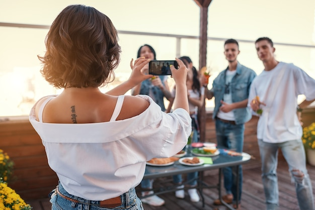 Memórias felizes, vista de trás de uma jovem tirando uma foto de seus amigos enquanto se divertia