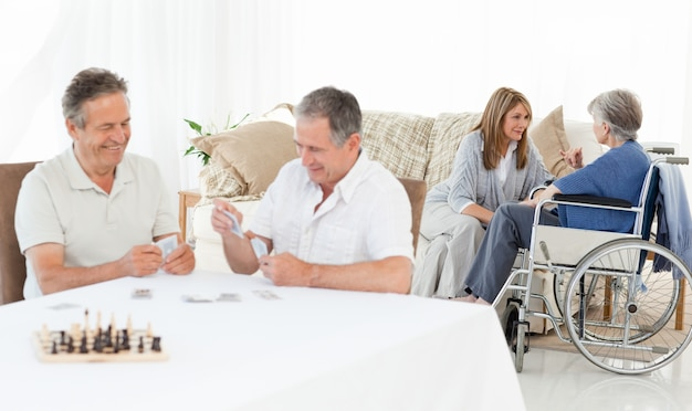 Men playing cards enquanto suas pessoas estão falando
