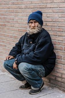 Mendigo barbudo em frente a uma parede de tijolos