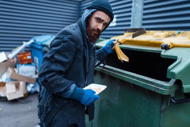 Mendigo barbudo procurando comida na lata de lixo