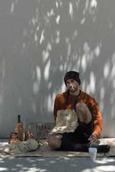 Mendigo com sinais de ajuda e álcool