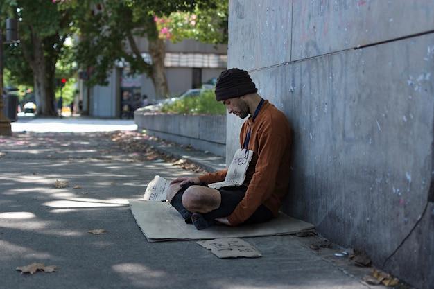 Mendigo de lado pedindo dinheiro a estranhos
