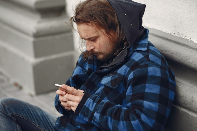 Mendigo em uma cidade de outono de roupas durty