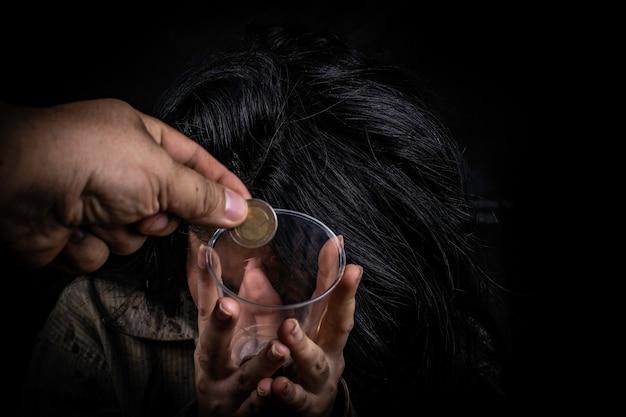 Mendigo sujo pedindo mão segurando algum dinheiro em fundo preto