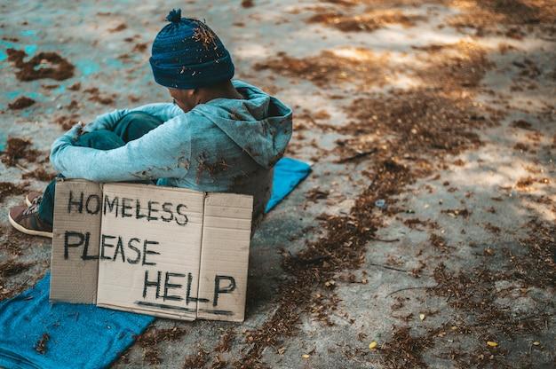 Mendigos sentados na rua com mensagens de sem-teto, por favor, ajudem.