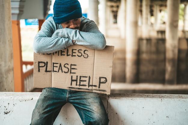 Mendigos sentam-se em barreiras com os sem-teto por favor, ajude as mensagens.