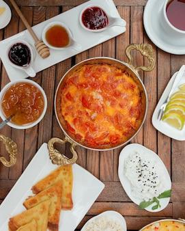 Menemen turcos em panela de cobre em uma mesa de café da manhã.