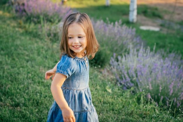 Menina 3-4 de cabelos escuros em vestido jeans ao sol dançando ou correndo e sorrindo, entre grandes arbustos de lilás