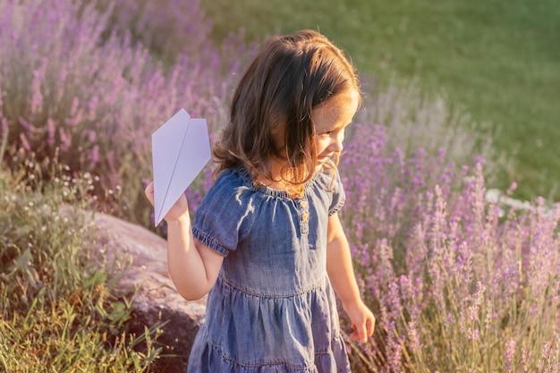 Menina 3-4 de cabelos escuros em vestido jeans ao sol lança avião de papel, entre grandes arbustos de lavanda lilás