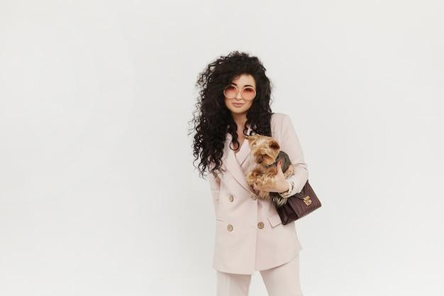 Menina à moda no equipamento oficial que guarda o cão pequeno bonito em suas mãos e que levanta no fundo branco, isolado. conceito de moda urbana.