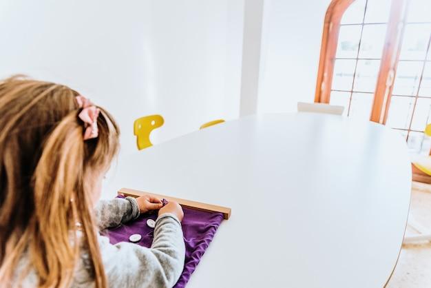 Menina abotoando um quadro montessori para desenvolver a destreza de seus dedos.