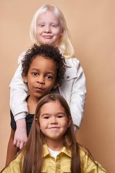 Menina abraça amigos mais jovens, garoto afro e garota caucasiana