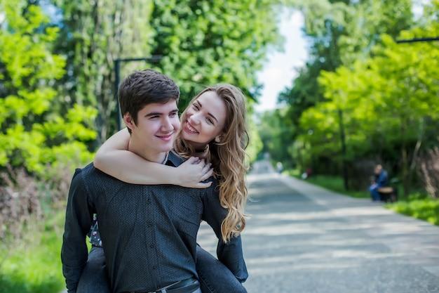 Menina abraça o cara por trás. casal feliz na caminhada