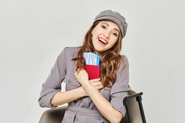 Menina abraça o passaporte com bilhetes e sorrisos.