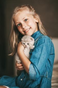 Menina abraça um gatinho britânico