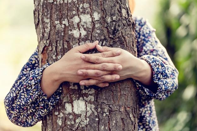 Menina abraçando a árvore