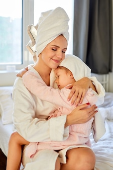 Menina abraçando a mãe depois do banho, eles se sentam juntos na cama, vestindo uma toalha na cabeça e um roupão branco. em casa, ambiente doméstico