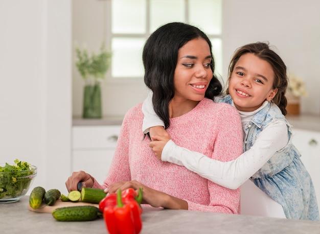Menina, abraçando a mãe enquanto cozinha