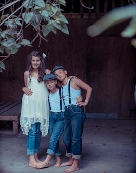 Menina abraçando dois irmãos cercada por cercas e vegetação